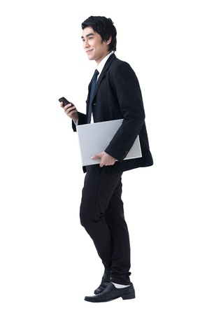 A young business man standing with laptop and phone photo