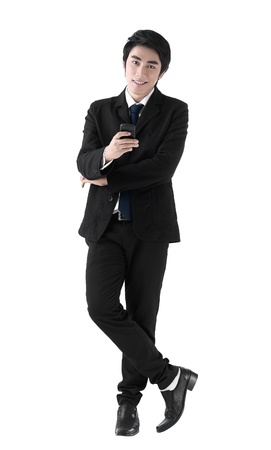 A young business man standing with the cell phone in his hand photo