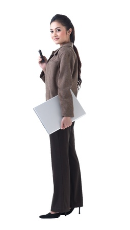 A beautiful business woman standing with laptop and on the phone photo