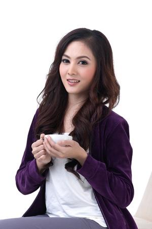 mujer sola: Una hermosa mujer joven sentada y sosteniendo una taza de caf�