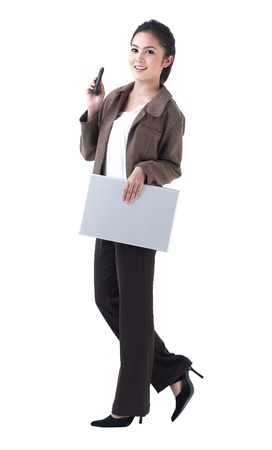 A beautiful business woman walking with laptop and on the phone photo