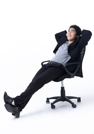 office life: Relaxed young business man sitting on the chair