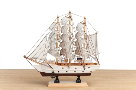 Wooden model of ship on the table with white background photo