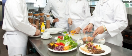 chefs whites: A senior chef giving cooking lesson to young chefs