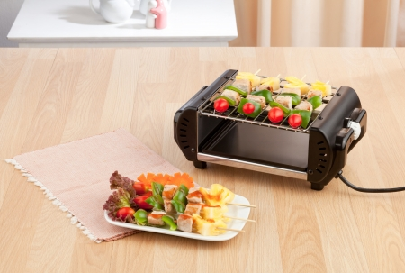 electric grill stove with barbecue display on wooden table photo