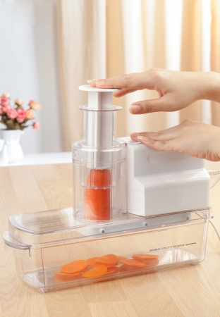 slicer: housewifes hands slicing carrot by eclectric slicer machine Stock Photo