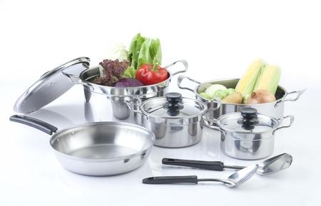 Set di pentole in acciaio con coperchi e verdura