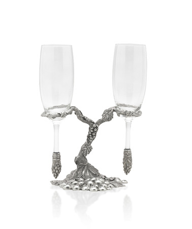 A pair of wine glasses hang on beautiful pewter stand isolated on white Stock Photo