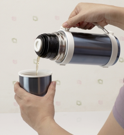 Pouring hot tea from thermos into cup photo