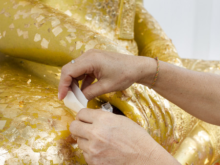 pastes: woman pastes adhesive gold leaf on golden buddha statue