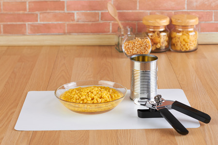 opener: can opener and bowl of canned corn in the kitchen