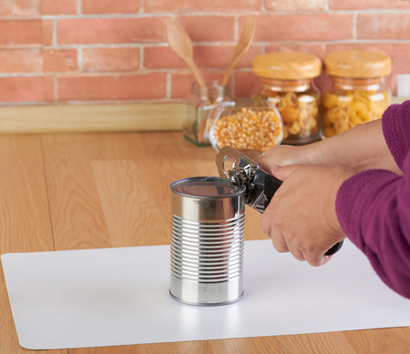 can opener: woman opening a can of corn with can opener in the kitchen