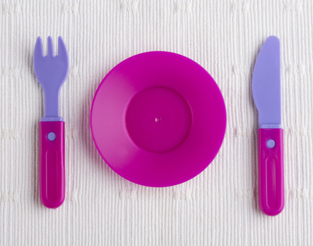 baby cutlery: plastic tableware toys isolated on white cloth