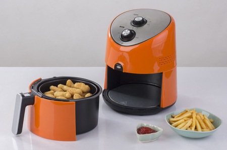 Air fryer machine with chicken and french fried Foto de archivo