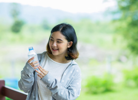 Happy asian girl holding a bottle of cold water Stock Photo