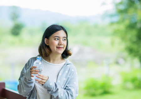 Pretty young asain girl holding a bottle of cold water Stock Photo