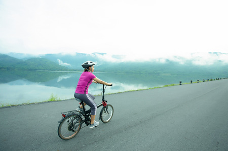 Young asian sport girl cycling on the lakeside in the morning