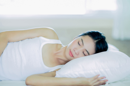 Asain girl is sleeping on the white bed