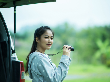 Young asian girl holding binoculars with happiness