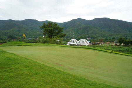 view at the beautiful golf course with white bridge railway, Tha Chom Phu bridge background in Mae Tha district, Lumphun, Thailand 免版税图像