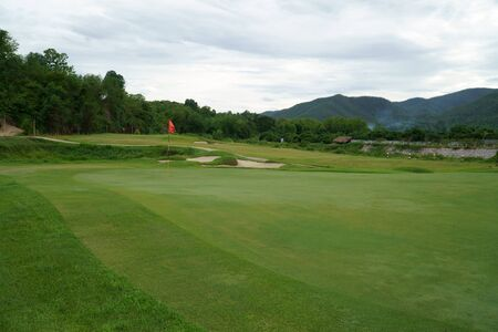 Red flag and sand bunker at the beautiful golf course at the mountain side with cloudy sky