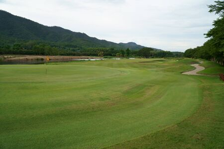Golfcourse, beautiful landscape of a golf court with green grass and mountain background