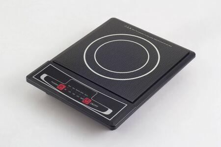 Placa de inducción portátil con panel táctil aislado sobre fondo blanco. Foto de archivo