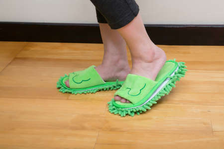 Close up image of woman feet with cute slippers standing on wooden floor