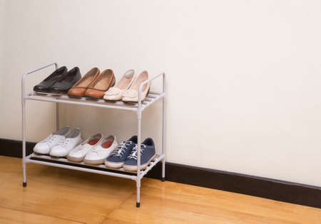 Small metal shoe shelf with women shoes on wooden floor in the room
