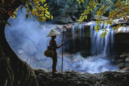 Portrait of Asian boy fisherman with waterfall in outdoors, Stock Photo