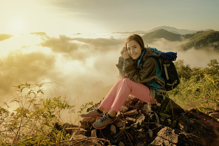The journey of adventure and thrill tourists..woman hike on the peak of rocks mountain at sunset, success,winner, leader concept,traveler with backpack.