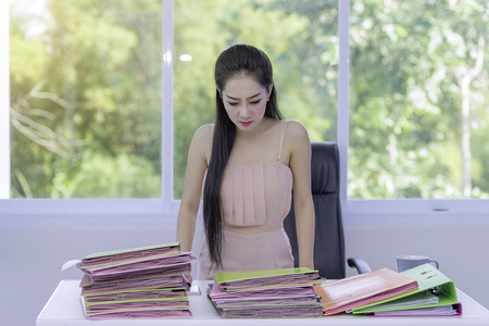 A beautiful young woman with a busy job,young woman working a lot document,the work of a busy girl. Stock Photo