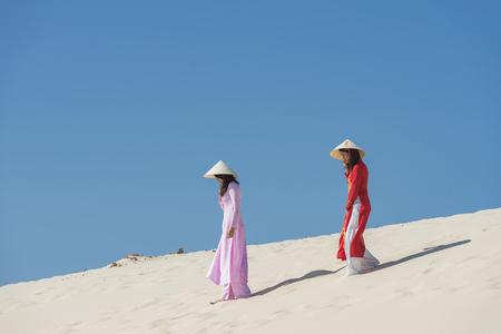 Vietnamese Ao dai dress walking on the white sand beach.