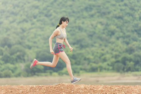 runner - woman running outdoors training for marathon run. Beautiful fit and asian fitness. Stock Photo - 73770767