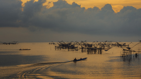 Sunrise over quiet sea, with only one boat fishing vessels that fish in the sea. Stock Photo