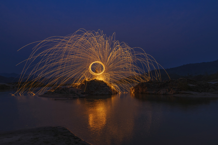 steel wool: Rotating lights,Color of fire swing on the stone at river in night time. Stock Photo