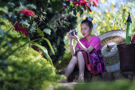 Hipster young girl with bright backpack looking at camera. View from  the tourist traveler on background mountain, flower,Beautiful girl and fresh flowers,tribe in beautiful costume dress,beautiful tribe girl.