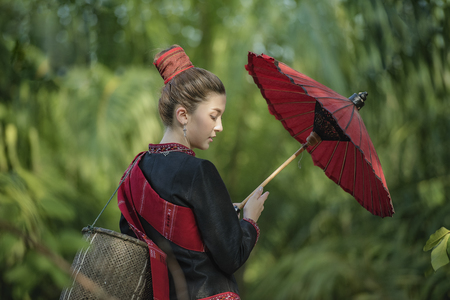country girl portrait holding a red umbrella in outdoors,beautiful happy Asian girl smile and laugh together.