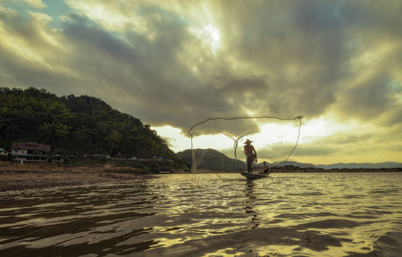 fisherman on wooden boat casting a net for catching freshwater fish Stock Photo