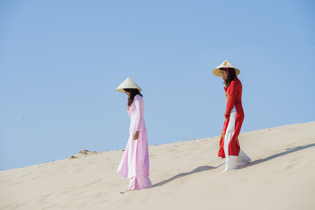 Beautiful woman with vietnam culture traditional ,vintage style,Ao Dai traditional,vietnamese women in Ao Dai traditional at white sand beach.