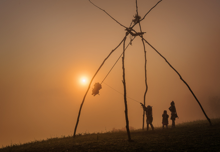 Tribal swings are sitting on a mountain with sun light . people playing with the wooden swing during the mountain Stock Photo