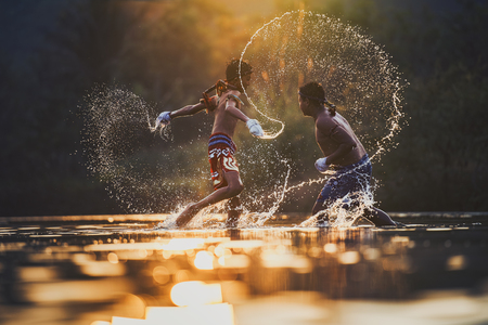 De vechter vastbindtape rond zijn hand voorbereiding om te vechten, Thai boksen aan de rivier, Boksen vechters trainning buiten, Muay Thai Stockfoto - 87160482