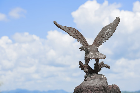 close up eagle on blue sky background,Eagle statue on the cliff.