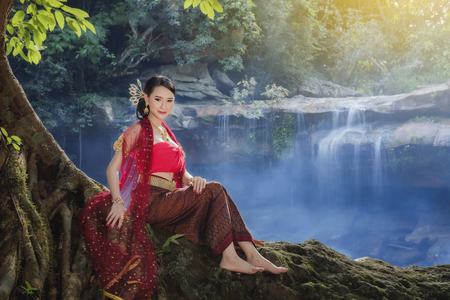Thai traditional uniform dress,women wearing typical Thai dress at waterfall,identity culture of Thailand. Stock Photo