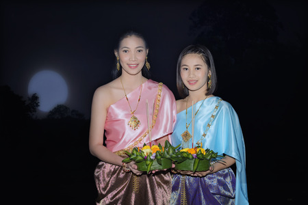 People with flower and candle to light and float on water to celebrate Loy Krathong Festival,Beautiful woman in Thai traditional with Krathong pray at the river,Bangkok, Ayutthaya,Chiang Mai,Thailand. Stock Photo