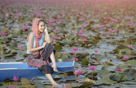 Asian girl in the lake of lotus flowers. Woman wearing traditional, Thai people, Pretty girl with the sea of red lotus, Udon Thani, Thailand, Unseen Thailand, travel concept, The Lake of water lily in sunrise