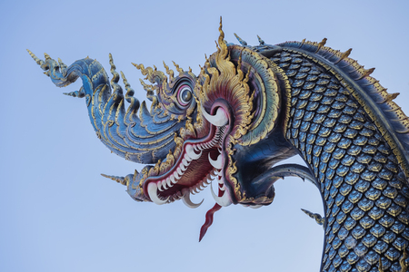 Serpent king or king of naga statue in Thai temple isolated on blue background,big snake thai art graphic in the temple,(The word naga means cobra in Sanskrit.) Stock Photo