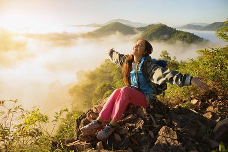 De avonturier staat op de top van de berg met mistige ochtendhemel met de schaduw van een verre berg, het concept van de levensstijl van de vrijheid levensstijl met rugzakken ontspannen. Stockfoto