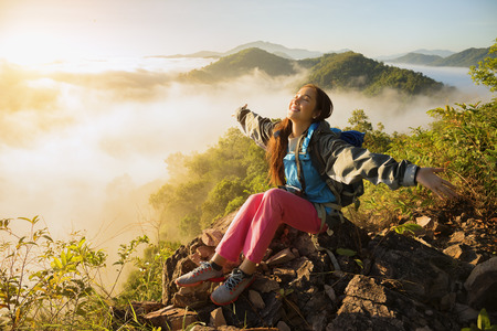 The adventurer stands at the top of the mountain with foggy morning sky with the shadow of a distant mountain,freedom lifestyle concept traveller with backpacks relaxing. Archivio Fotografico