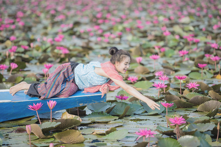 Asian girl in the lake of lotus flowers,Woman wearing traditional,Thai people,Pretty girl with the sea of red lotus,Udon Thani,Thailand,Unseen Thailand,travel concept,The Lake of water lily in sunrise